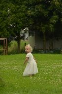 little girl plays on green grass