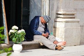 barefoot old man sleeps at Church, italy, Rome