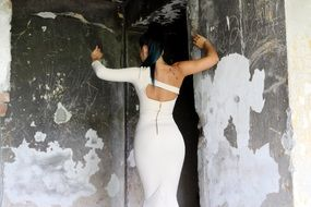 photo of the back of a brunette in a white dress on a background of concrete walls