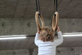 baby holds on to gymnastic rings