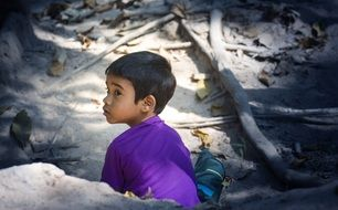 child sits behind a stone in a purple t-shirt