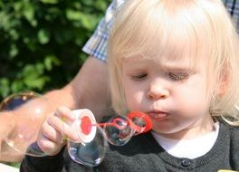 young girl making soap bubbles