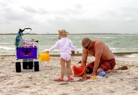 dad with a child on a sandy beach