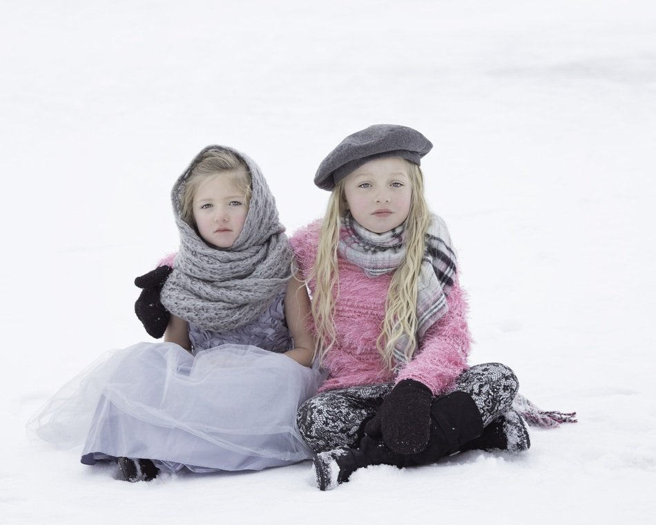 Sisters, two Child Girls sitting on snow
