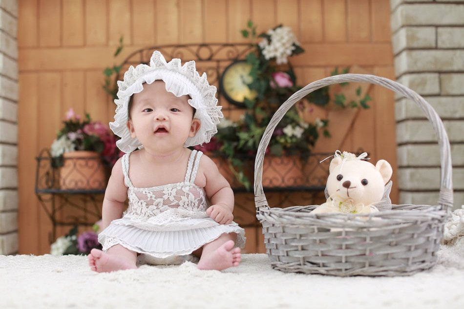 baby in white cap near the basket