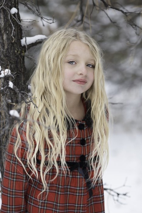 beautiful photo of a cute girl in a snowy forest