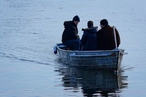 three people in a boat in a winter lake
