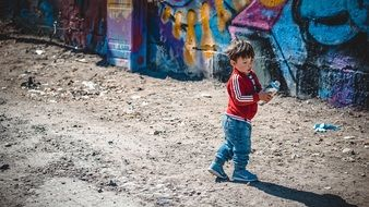 little boy stands near the wall with graffiti