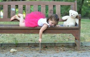 little girl lying on a bench in the park