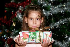 little girl with a gift near a shiny Christmas tree