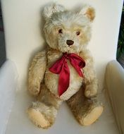 teddy bear with a red bow in a chair