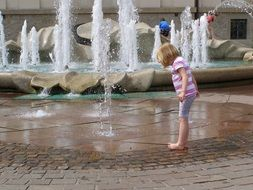 little girl playing in fountain