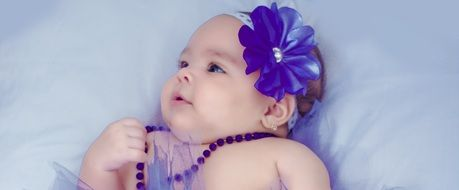 portrait of a baby girl with purple accessories