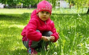 little girl squatting on green grass
