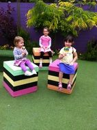 children sit on colorful cubes in the yard