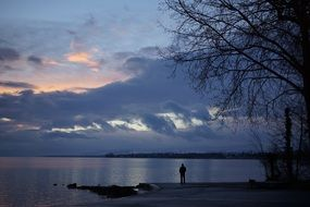 man stands on the shore of Lake Geneva against the evening sky in Switzerland