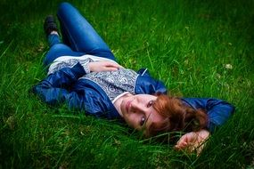 woman lying on the green grass
