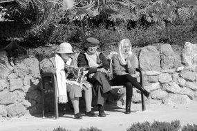 old people relaxing on a bench on a sunny day