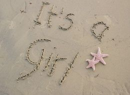 It\'s a girl text on a sand