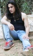 A man with long hair posing while sitting on the ground