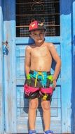 Child Boy in bright pants stands at Blue Door
