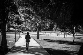 a lonely girl walks along a path in a park