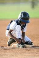 baseball player is tying shoelaces on the field