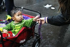 Asian Baby Boy in a colorful carriage with toys outdoors in New Orleans