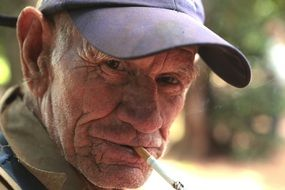 old man in a cap smokes