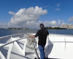 Man on yacht in sea looks at city, usa, florida, miami