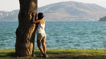 girl stands by a lonely tree by the sea