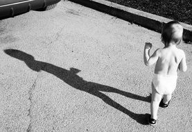black and white photo of a child with a shadow