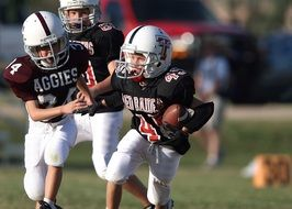 children in helmets play American football