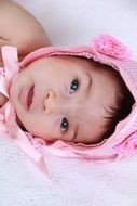 photo of a newborn in a pink cap