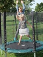 two children in a trampoline among nature