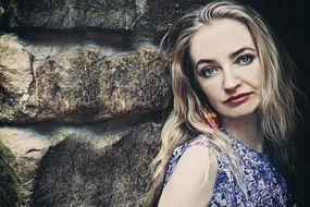 photo of a blonde against a stone wall