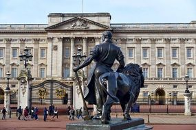 man with hammer and lion, bronze statue at Buckingham Palace facade, uk, London