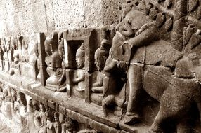 figures of people and animals on the wall of the temple in cambodia