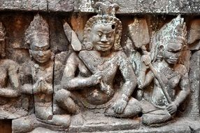 figures of warriors on the wall of the temple in Cambodia