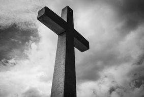 black and white photo of a stone cross against a cloudy sky