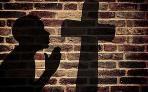 shadows from the cross and prayer on a brick wall