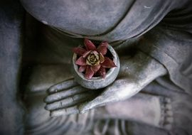 statue of meditating Buddha with flower in hand