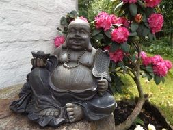 bush of rhododendron and buddha statue