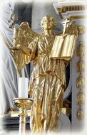 golden angel with a bible near a candle