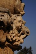 statue with heads on a column