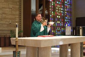 priest with a cup at the altar