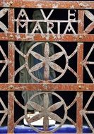 Ave Maria, wrought iron lettering on aged grates