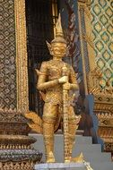 golden statue of the devil near the temple