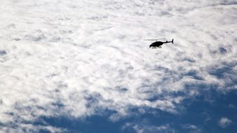 helicopter flies under white clouds