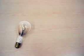 Dimmed Light Bulb at wooden background